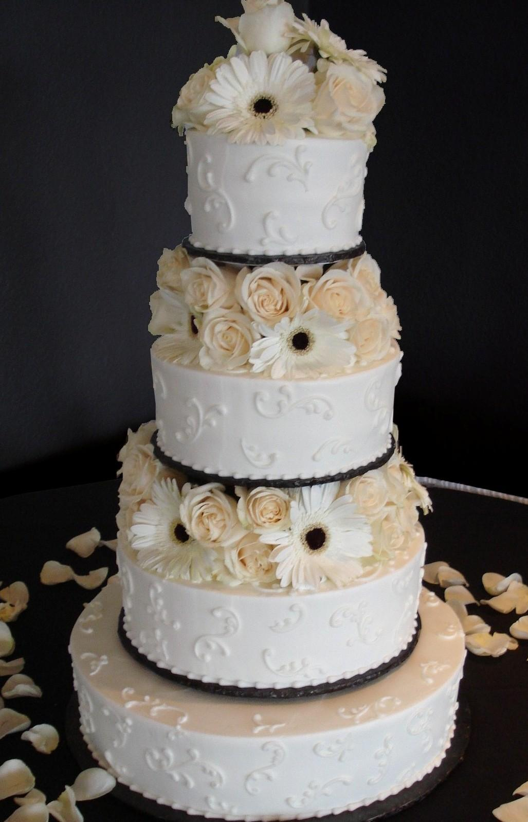 White Ercream Iced 4 Tier Round Wedding Cake Decorated With A Sporadic Scroll Work
