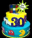 Totally 80's Birthday cake,  Blue and yellow buttercream iced, 2 round tiers with 80's memorable. Decorated with the fun Rubik's cube, the original pacman, cassette tapes, and of course, a corvette.  Everything on this cake is EDIBLE. (Serves 28-55 party slices)