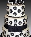 Black Flowers White Pearls 40th Birthday Cake. White buttercream iced, round, 3 tiers decorated with black flowers with white pearl centers, ribbon and bow. Everything on this cake is edible. (Serves 48-135 party slices)
