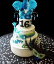Mardi Gras Sweet 16 Birthday Cake,  White buttercream iced, 3 round tiers adorned atop a rhinestone cake base decorated with fondant ribbons, mardi gras masks, jewels, pastel pearls and feathers. (Serves 48-135 party slices) We highly discourage the use of feathers on cakes but will make the accommodation at your request.