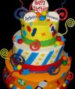 Gumball Machine 1st Birthday cake, Yellow, White and Orange Buttercream iced, 3 tiers adorned with gumball candy, Chocolate swirls, Fondant balloon cutouts, ribbons and stripes.