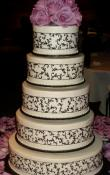 White buttercream iced,  5 tier round wedding cake decorated with black piped scrollwork ribbon.  Fresh Roses as the topper.   (This cake can serve receptions with 250-380 expected guests)