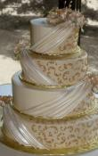 Candlelight buttercream iced,  4 tier round wedding cake decorated with Pearlescent Fondant Drapes, Gold Piped scrolls, and Gumpaste flowers. (This cake can serve receptions with 180-325 expected guests)