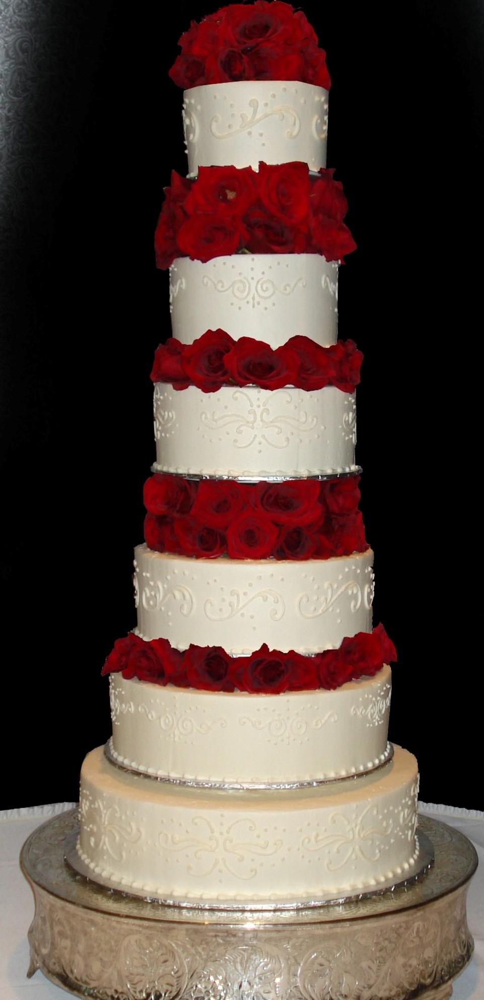 Candlelight Buttercream Iced 6 Tier Round Wedding Cake Decorated With White Variegated Patterned Scrolls